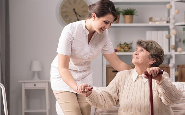 Nurse assisting elderly woman.