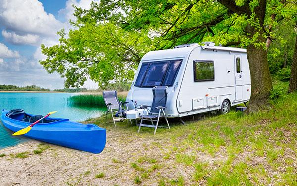 Caravan and canoe by scenic lake.