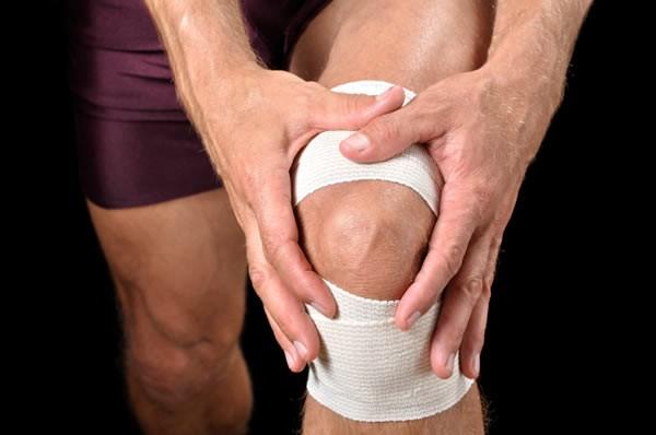 Sportsman holding bandaged knee