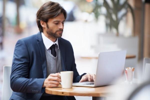 Man working on laptop computer at desk.