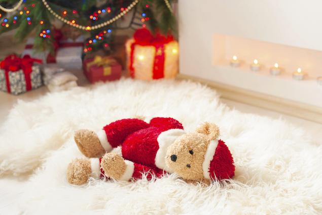 Santa teddy bear toy on sheepskin near illuminated christmas tree