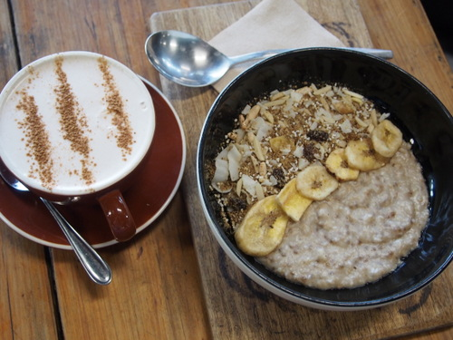 A bowl of chia coconut and banana porridge with an almond milk chai latte