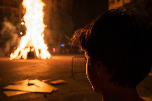 Boy looking at a bonfire, Barcelona. Photo: iStock