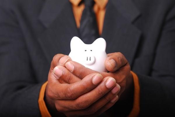 Man holding white ceramic piggy bank