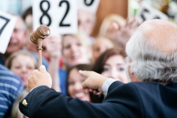 Auctioneer holding gavel as bidders look on at auction