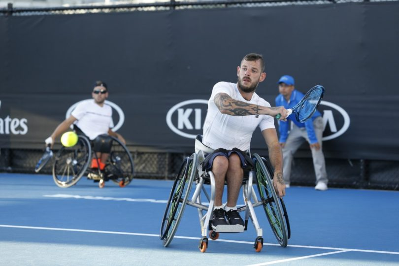 Man playing tennis in a wheelchair.