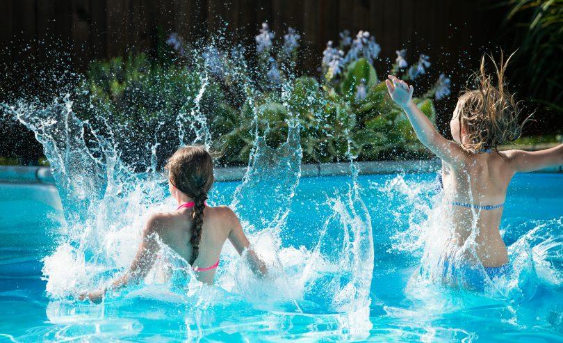 Two children playing in backyard swimming pool.