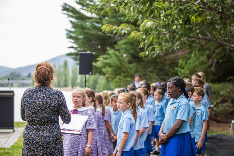 Schoolchildren sing <em>Give Peace a Chance</em> at the ceremony.