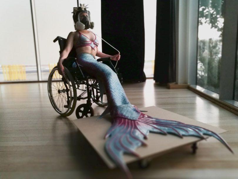 Mermaid wearing breathing apparatus, seated in wheelchair.
