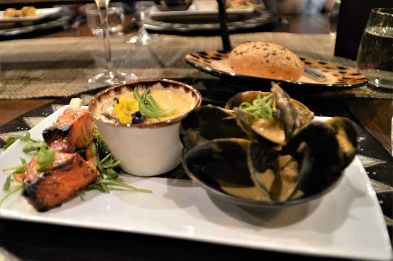 An entree tasting plate of yellow curry coconut mussels, Miso and honey-cured salmon sosatie and egg custard with blue swimmer crab.