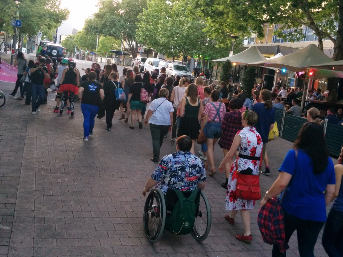 Group of women of all ages, including one on roller skates in a tutu, and one in a wheelchair, walking through Garema Place in the city as part of a Reclaim the Night rally.