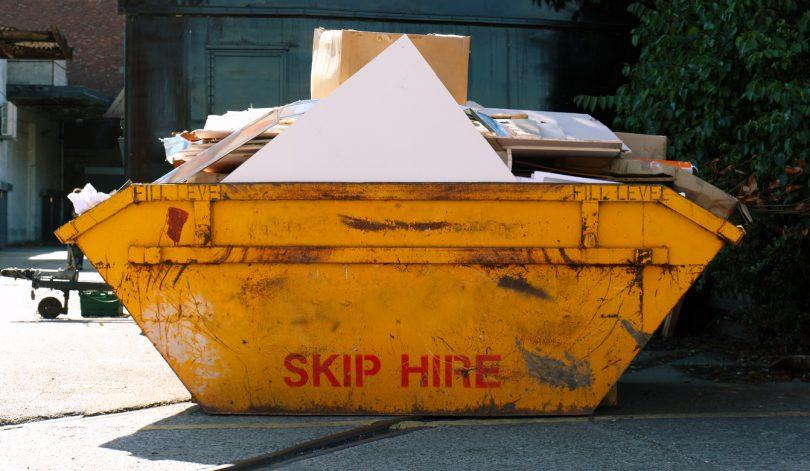 Yellow skip bin full of building waste.