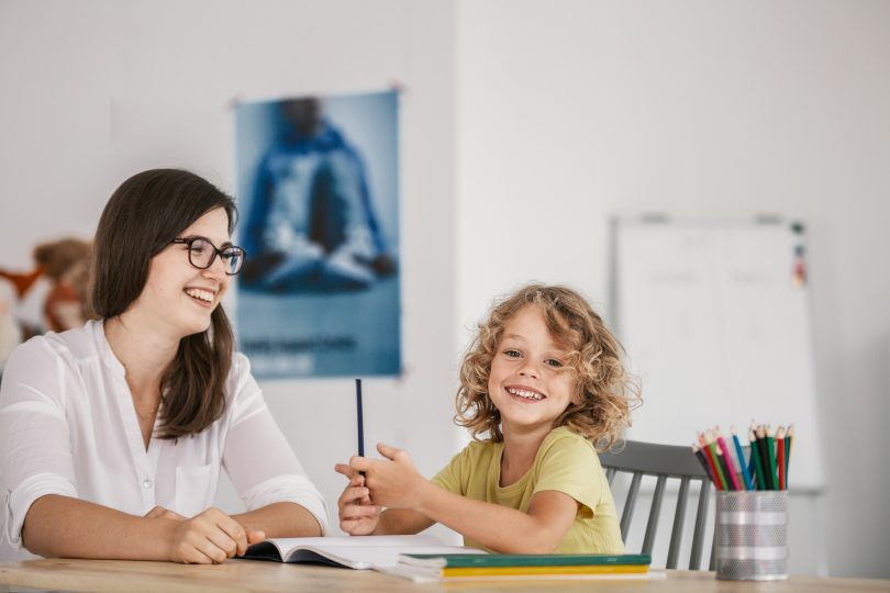 Smiling teacher and happy kid doing homework after classes