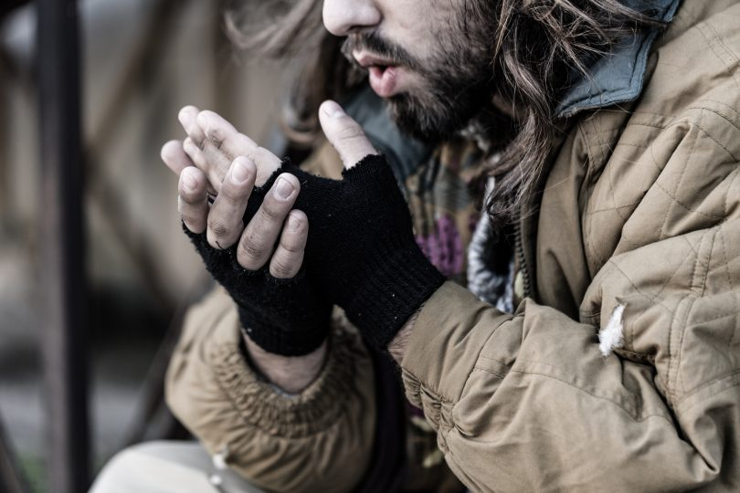 Homeless man blowing on hands to keep warm.