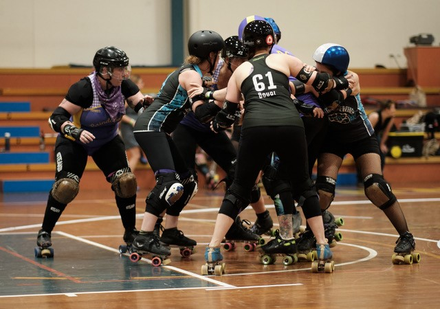 Brindabelters and Black and Blue Belles players in a pack playing for 3rd place