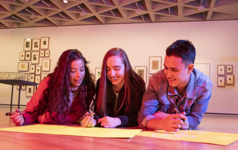 Photograph shows three teenagers lying on the ground drawing in a gallery