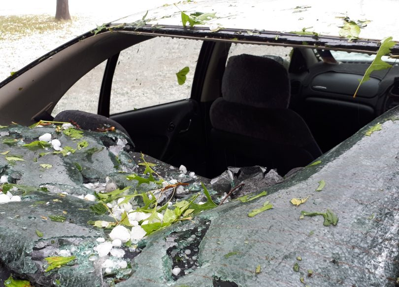 Car with smashed windscreen from hail.