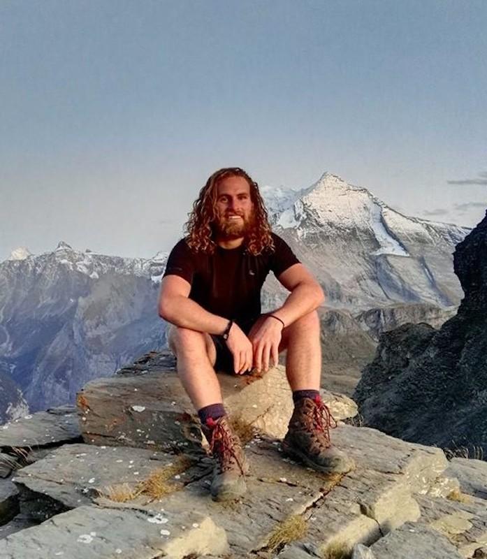 Montana O'Neill sitting atop a mountain
