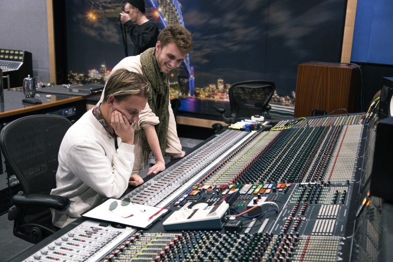 Photograph shows two people at mixing desk