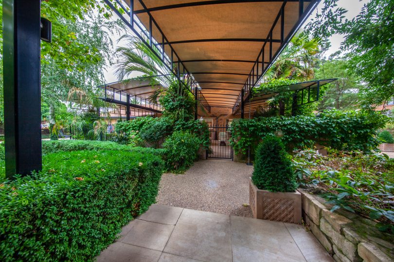 Evergreen shrubs and a covered walkway lead to the outdoor entertaining area