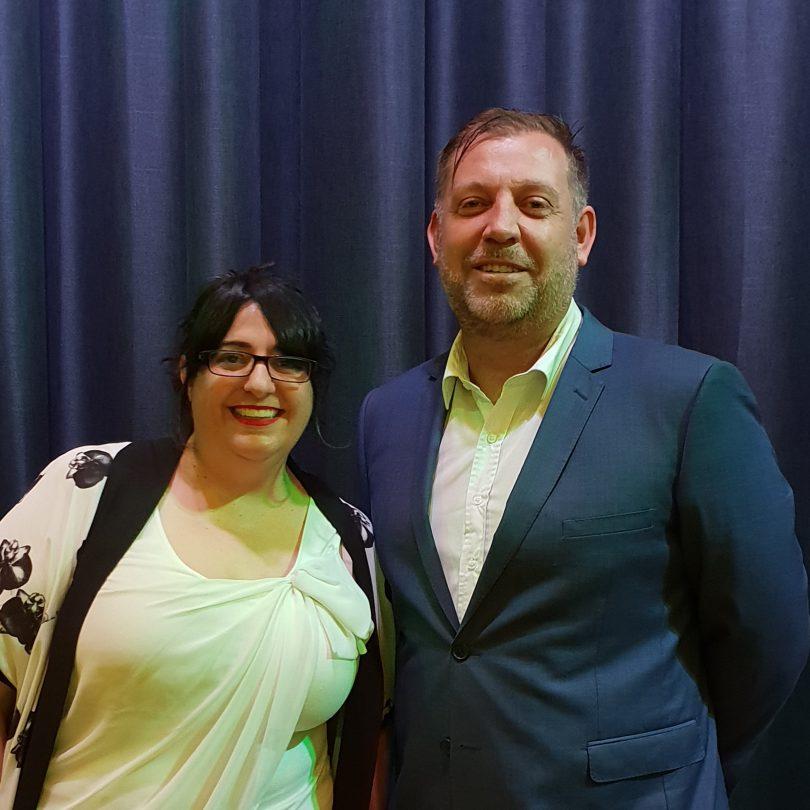 Nadia Pessarossi with Rubik3 founder and senior partner Guy Earnshaw, standing against blue curtain, smiling.