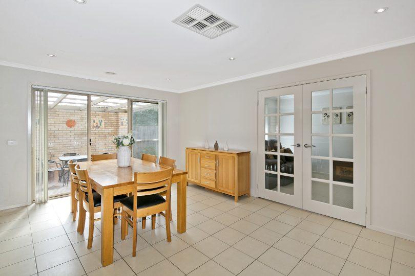 Dining room with the versatile rumpus room through glass doors.