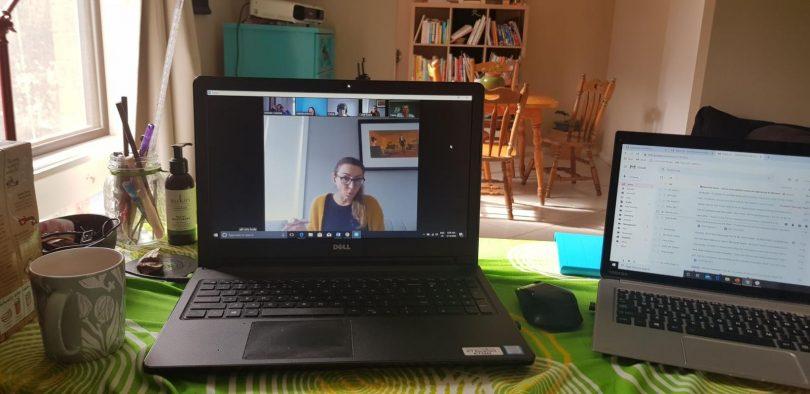 Laptop in home displaying Zoom meeting.