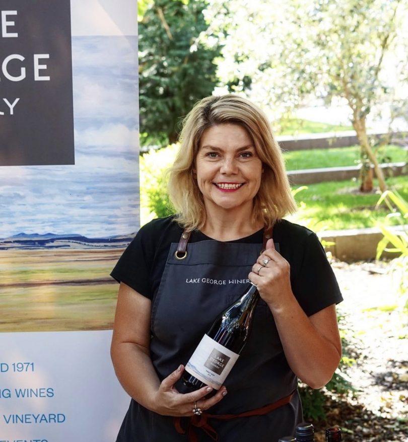 Sarah McDougall holding bottle of red wine.