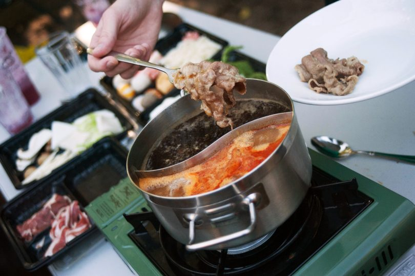 Cooked beef being removed from pot of soup.