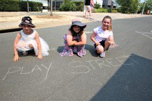 "Three children kneeling on street in front of ""Play Street"" written in chalk."