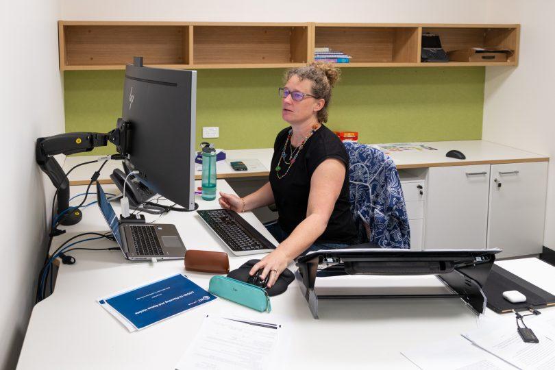 Dr Kerryn Coleman sitting at work desk.