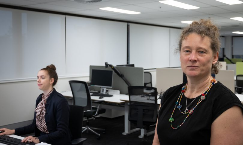 Dr Kerryn Coleman (right) in office with colleague behind desk.