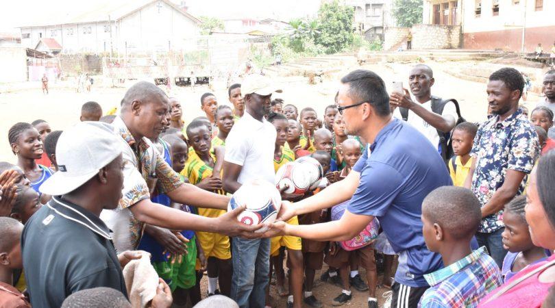 "Kitsana ""Jimmy"" Muongsene handing over a donated football an African community."