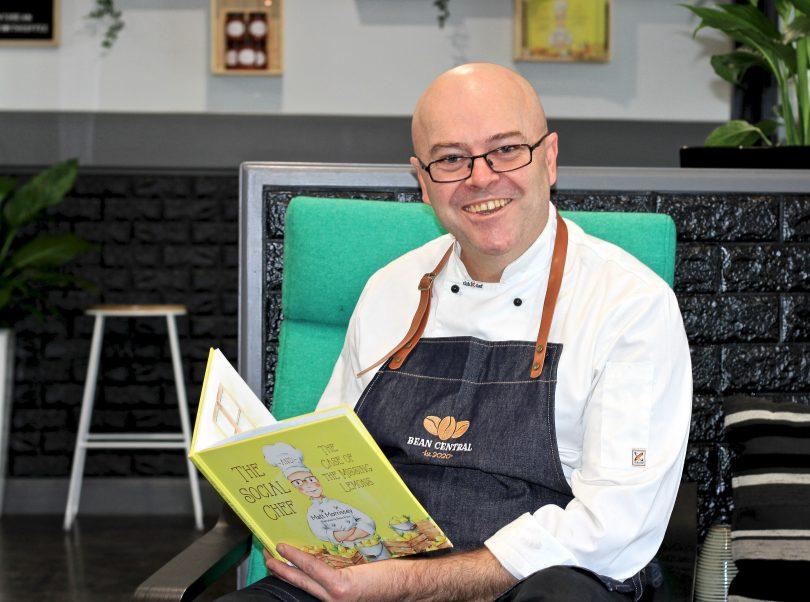 Matt Morrissey sitting down in Central Bean cafe holding children's book he wrote.
