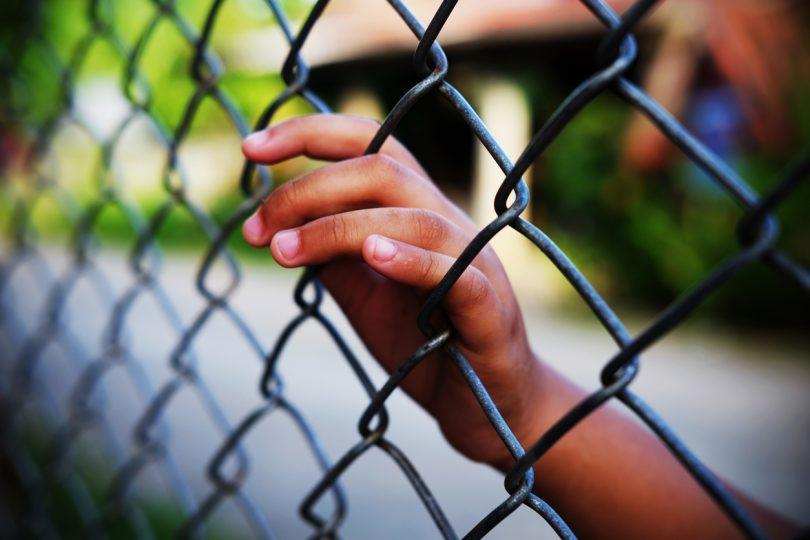 Child behind wire