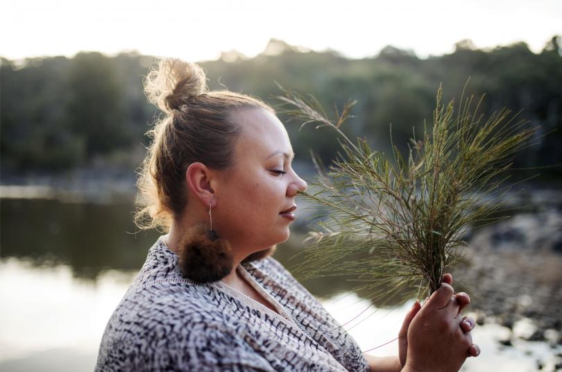 Krystal Hurst outdoors holding native plant.