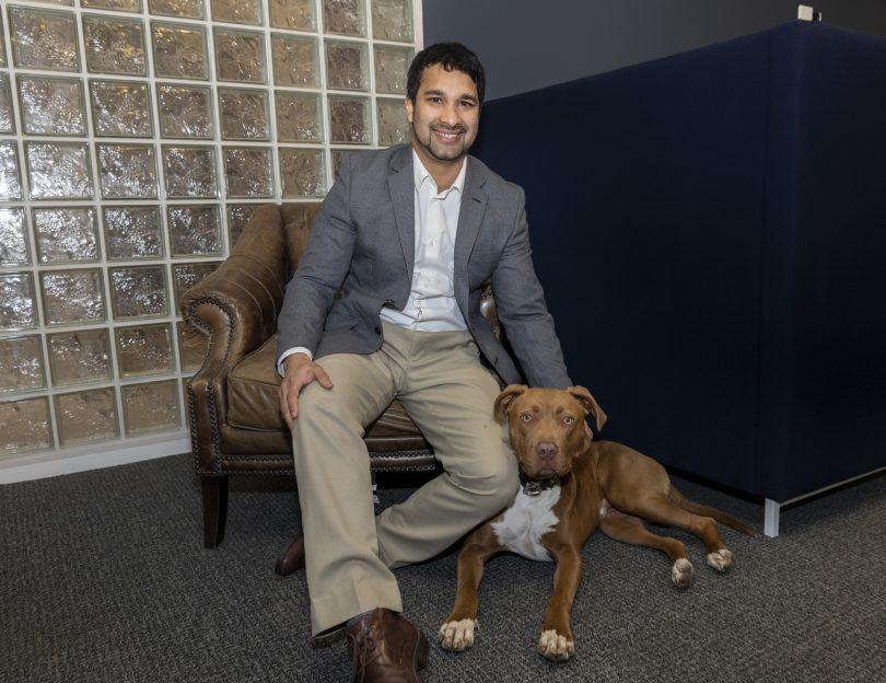 Kirk Fonseca sitting with his dog, Roman.