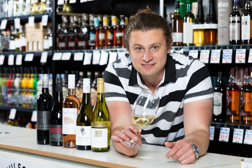 Dave Winmill holding glass of wine behind counter at Farrah's Liquor Collective.