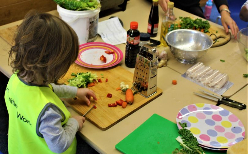 Child slicing vegetables in playgroup.