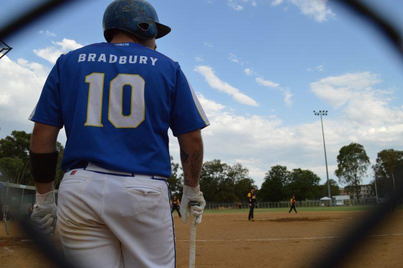 Rear view of Jarrod Bradbury standing on softball field as seen through fence.