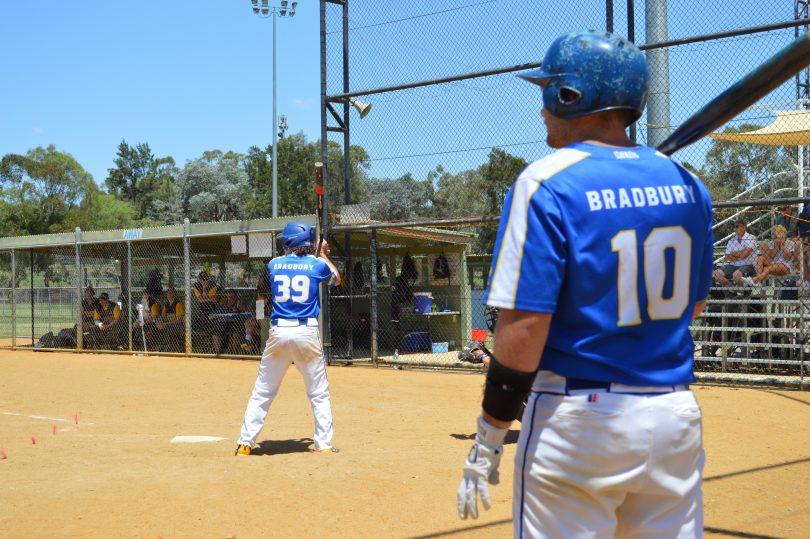 Jarrod Bradbury watching his brother, Jeremy, batting in game of softball.
