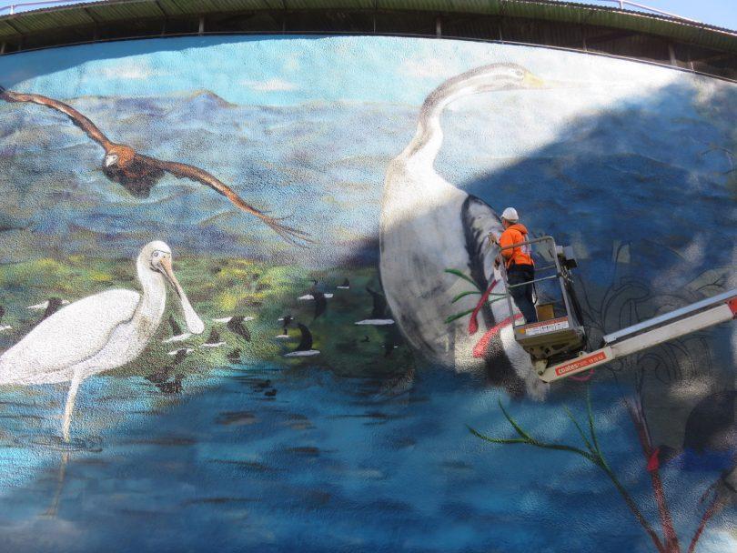 Street artist paints water tower