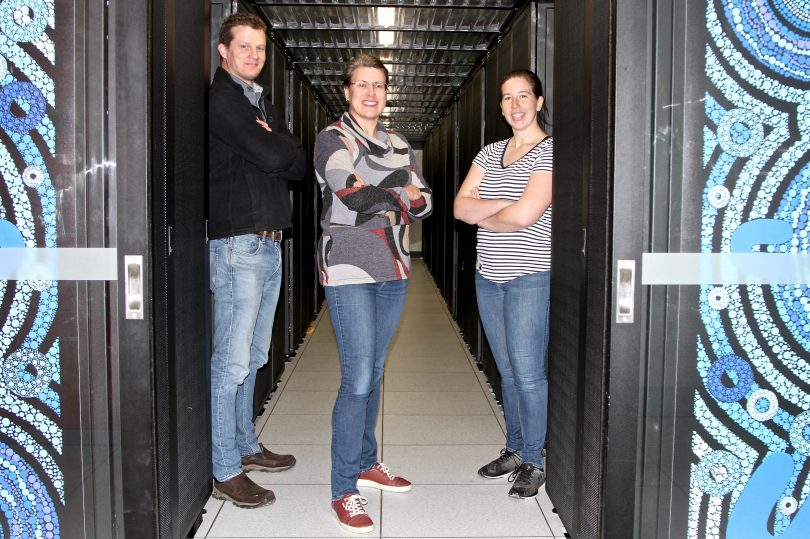 From left: Dr Stephen Fairweather, Associate Professor Megan O'Mara and Dr Katie Wilson with the Gadi supercomputer.