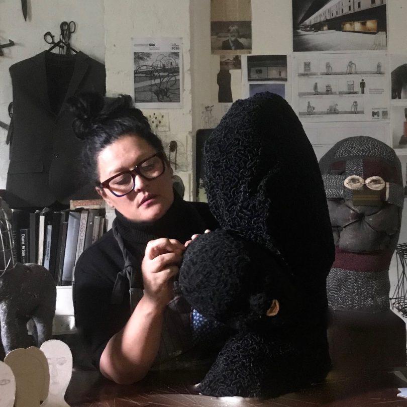 Visual artist Mariana del Castillo hand stitching large black sculpture.
