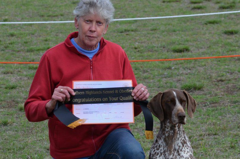 Christine Forsyth kneeling with dog Ziggy holding certificate.