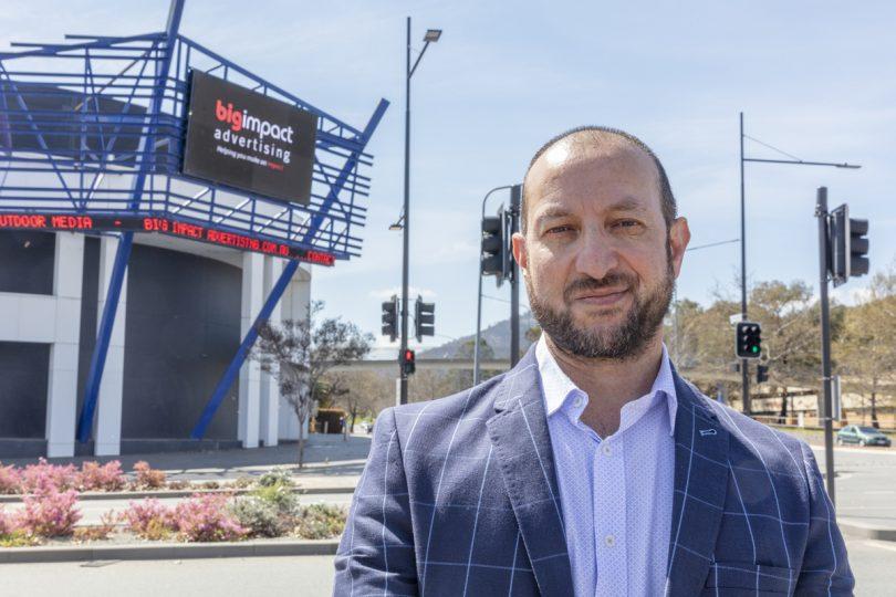 MJ Qual standing in front of digital billboard.