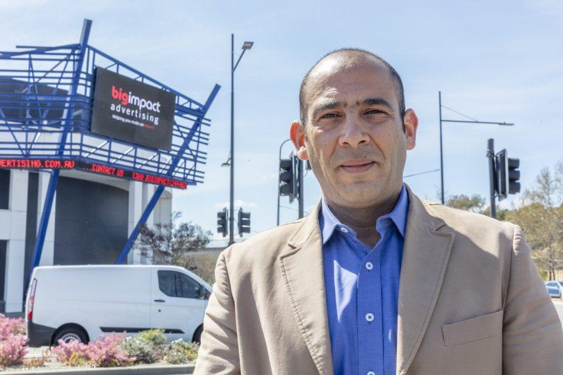 Tam Bakr standing in front of digital billboard.