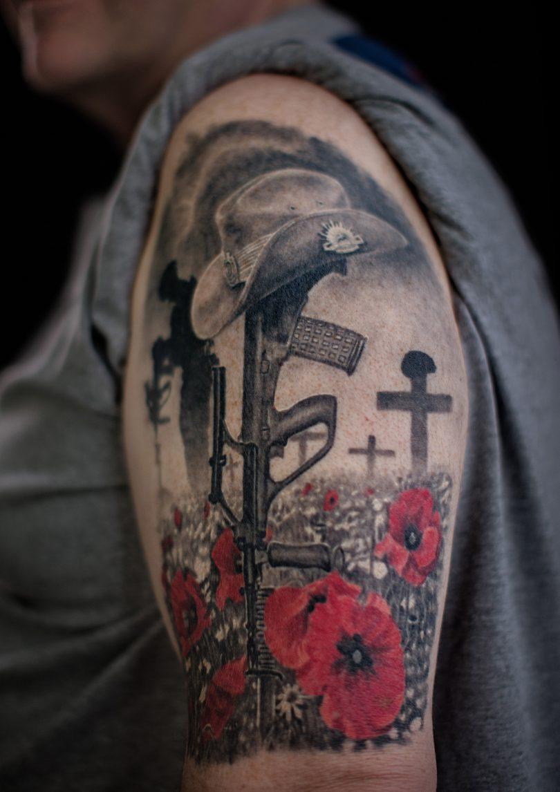 Veteran displaying military tattoo on arm.
