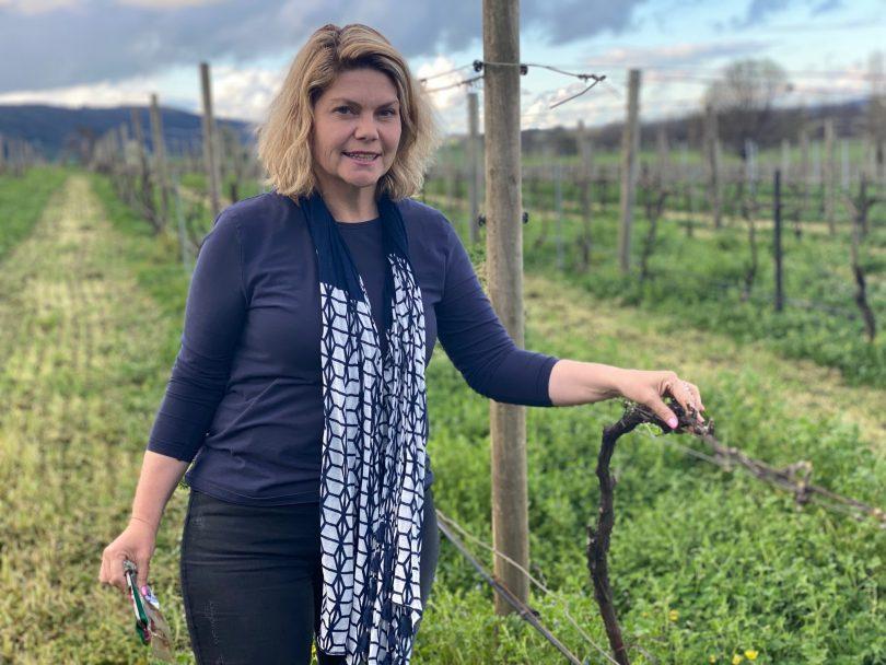 Lake George Winery owner Sarah McDougall standing in vineyard.