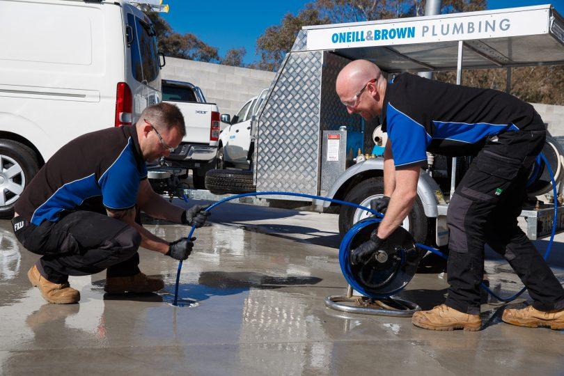 Plumbers feeding hose into drain.